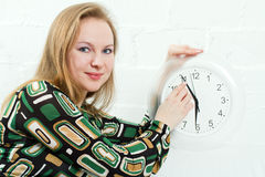Young woman and clock. Young woman show time on clock Royalty Free Stock Photo