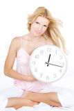 Young woman with clock on the bed Royalty Free Stock Image