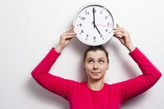 Young woman with clock over her head. Watch the time concept. girl is holding round white clock against white wall background. Stock Image