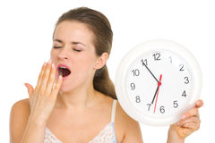 Young woman with clock yawing after sleep Stock Images