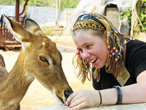 Young woman close encounter wild deer Asia. A unique image of a pretty young girl who is on holiday in Thailand, Asia at the Tiger Temple outside of Bangkok city Stock Photos