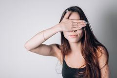 Young woman close her eyes with hand. Young woman close her eyes with hand on white background Stock Photo