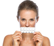 Young woman close mouth with pack of pills Stock Image