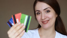 Young woman close-up holding credit bank cards and smilling. The concept of credit finance, economy and shopping. Internet stock footage
