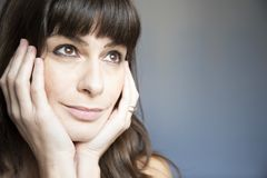 Young woman close-up portrait. Caucasian with brown long hair and bangs. Serene expression, looking up with hands on face and copyspace stock photos