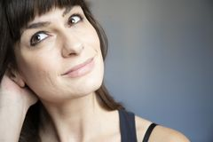 Young woman close-up portrait. Caucasian with brown long hair and bangs. Smiling expression, looking up right with one hand behind neck. Copy space royalty free stock photos