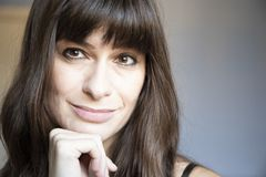Young woman close-up portrait. Caucasian with brown long hair and bangs. Smiling expression, with one hand under the face royalty free stock photography