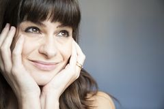 Young woman close-up portrait. Caucasian with brown long hair and bangs. Smiling expression, looking up with both hands on face. copyspace royalty free stock photography