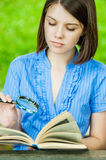 Young woman close-up reading book magnifier Stock Images