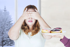 Young woman closed eyes for donuts. Portrait of young woman closed her eyes for a plate of donuts with winter background on the window Royalty Free Stock Images