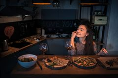 Young woman with closed eyes sits at the table with food and win. E in the modern kitchen. Cute brunette alone dinning and dreaming in the stylish apartment Royalty Free Stock Photos