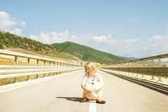 Young woman with closed eyes sitting down on road. Albania lanscape stock photo
