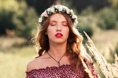 Young woman with closed eyes standing in meadow. Beautiful girl in wreath with makeup standing between spikelets. Relaxation, nirvana, unity with nature Royalty Free Stock Photo