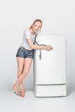Young woman and closed fridge Royalty Free Stock Photos