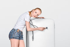 Young woman and closed fridge Stock Image
