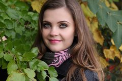Young woman closeup headshot next to fall leaves. Young woman with a smile and long hair, natural makeup, dressed for cool weather, wearing scarf and leather Stock Images