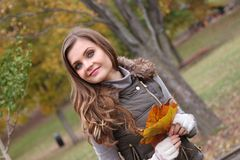 Young woman closeup holding leaves on a fall day. Young woman with a smile and long hair, natural makeup, dressed for cool weather, holds leaves in her hands Stock Photos