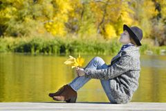 Young woman with closing eyes sitting on the pier, autumn leaves. In hands. Sunny day stock photo