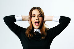 Young woman closing her ears and screaming Stock Images
