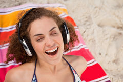 Young woman closing her eyes while listening to music Stock Photo