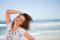 Young woman closing her eyes while standing on the beach Royalty Free Stock Images