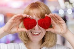A young woman is closing her eyes with two hearts stock photography