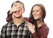 Young woman closing his boyfriend eyes. Royalty Free Stock Photo