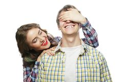 Young woman closing his boyfriend eyes. Stock Images