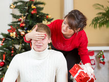 Young woman closing man eyes by her hands with gift Royalty Free Stock Image