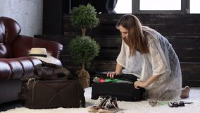 Young woman closing suitcase full of clothes Royalty Free Stock Images