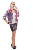 Young woman clothed in a leather skirt and shirt, on phone Royalty Free Stock Photos