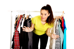 Young woman with clothes on hanger. Royalty Free Stock Images