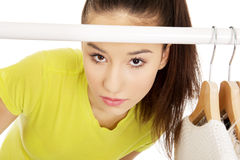Young woman with clothes on hanger. Royalty Free Stock Photos