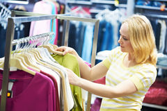 Young woman at clothes shopping store Stock Photos