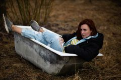 Young woman in clothes is taking an empty old bath in the middle of a forest stock photos
