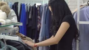 Young woman in a clothing store chooses a coat. Close-up.  stock video footage