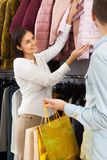 Young woman in a clothing store. Young women looks at the coat in a clothing store royalty free stock photos