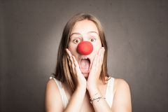 Young woman with a clown nose. On a grey background Royalty Free Stock Photography