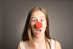 Woman with a clown nose. Young woman with a clown nose on a grey background Stock Image