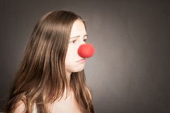 Young woman with a clown nose. On a grey background Royalty Free Stock Photos