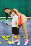 Young woman or coach teaching child how to play tennis on a court indoor Stock Image