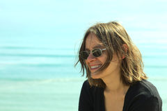Young Woman on Coast. Portrait of a smiling young woman in sunglasses on the coast (Selective Focus, Focus on the left side of the face Stock Photos