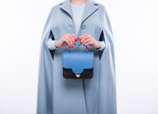 Young woman in a coat holding blue-black purse Royalty Free Stock Images