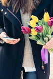 Young woman in coat holding a bouquet of tulips in one hand  Stock Photos