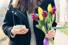Young woman in a coat holding a bouquet of tulips in one hand an Stock Images