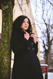 Young woman in coat near tree at street Stock Photography