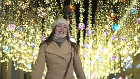 Young woman in a coat on the street under a garland. Slow motion stock footage