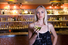 Young woman with cocktail in bar, portrait Royalty Free Stock Photo