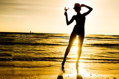 Young woman with cocktail on the beach in tropics on sunset sea Stock Photography
