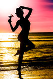 Young woman with cocktail on the beach in tropics on sunset sea Royalty Free Stock Photos